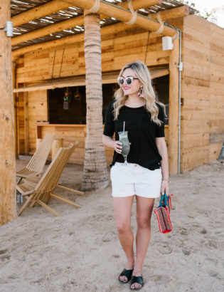 Travel blogger Bows & Sequins wearing a black Old Navy tee and white Old Navy shorts by a tiki hut in Cabo.