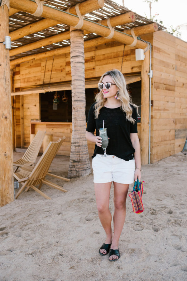 Travel blogger Bows & Sequins wearing a black tee and white shorts with colorful accessories by a tiki hut in Cabo.