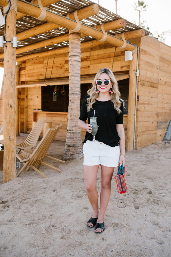 Bows & Sequins wearing a black and white Old Navy outfit with a colorful straw tote in Cabo San Lucas, Mexico.