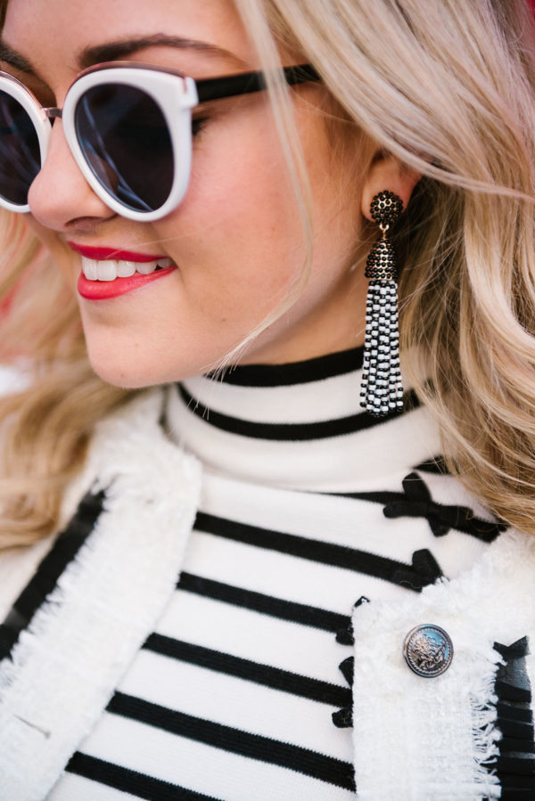 Bows & Sequins wearing black and white tassel earrings from BaubleBar.