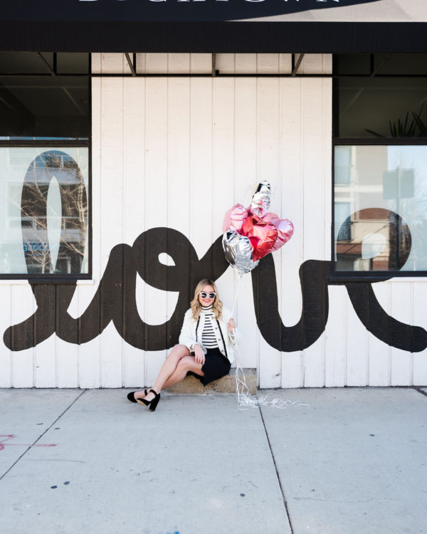 Bows & Sequins styling a black and white outfit for Valentine's Day in front of a LOVE mural l in Chicago.