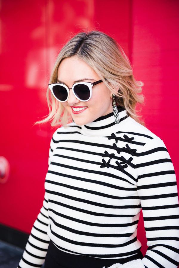 Bows & Sequins wearing a black and white striped turtleneck with bows.
