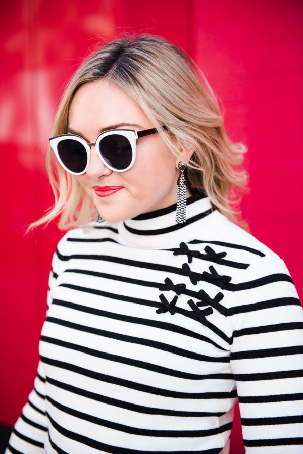 Bows & Sequins wearing a Maison Jules black and white striped turtleneck with bows and black and white sunglasses.
