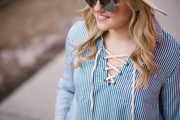 Bows & Sequins wearing a lace-up striped shirt.