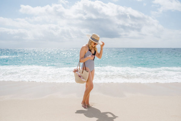 Travel blogger Bows & Sequins wearing a Jets by Jessika Allen striped swimsuit with a Clare V Kenya tote in Cabo San Lucas on the beach.
