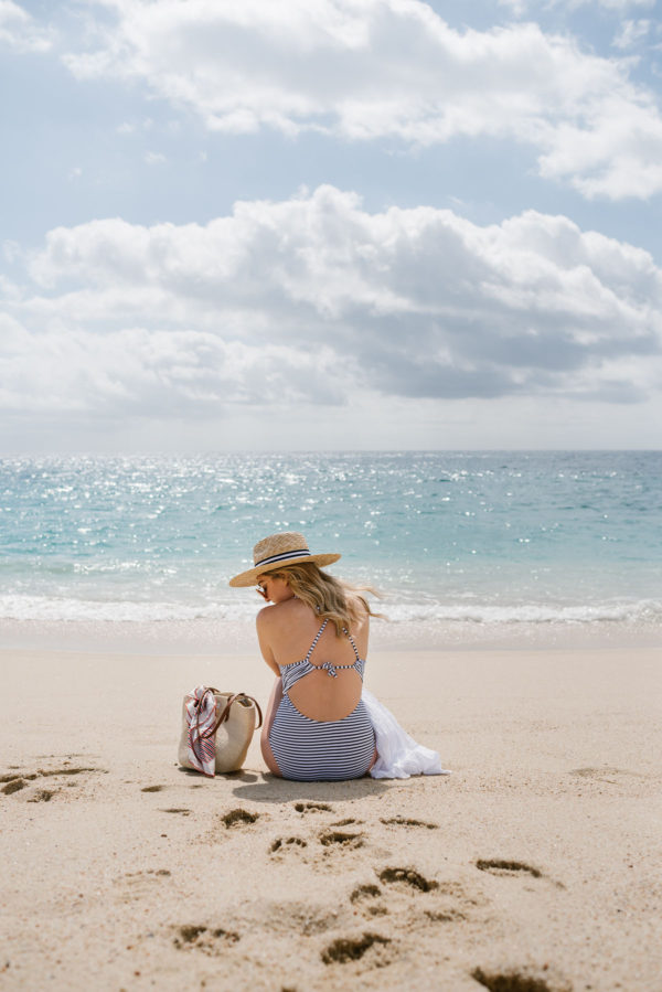 Bows & Sequins by the ocean on the beach wearing a navy striped one-piece swimsuit with a Hat Attack straw sunhat.