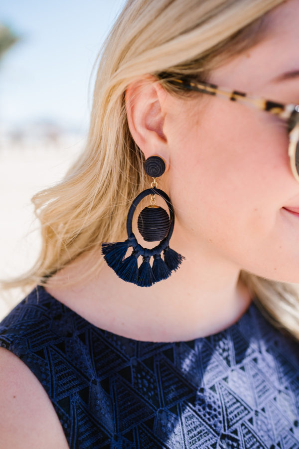 Bows & Sequins styling Tuckernuck dreamcatcher earrings on the beach in Cabo.