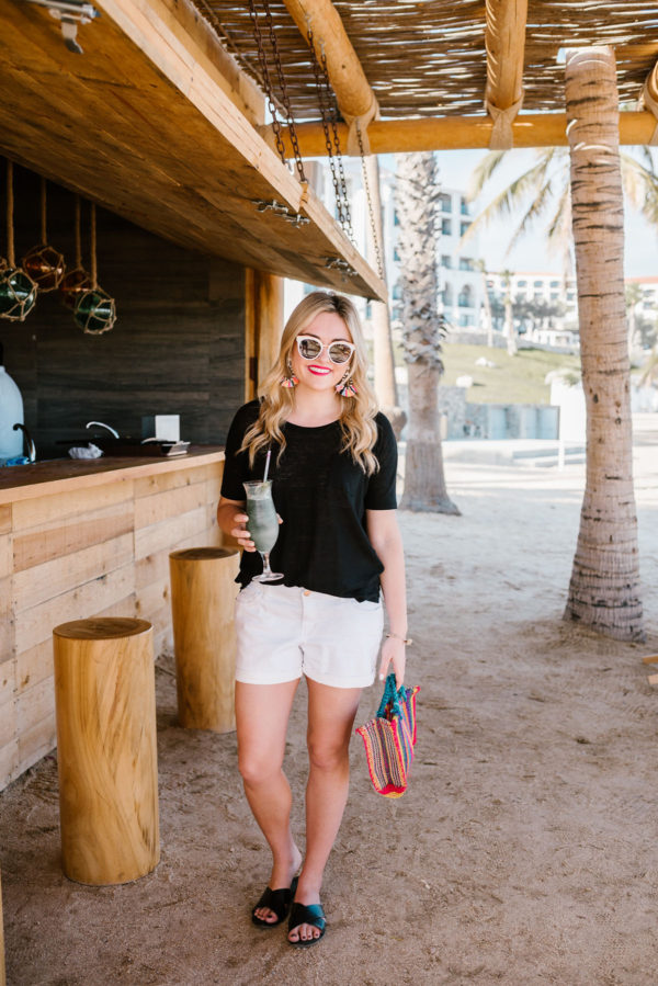 Bows & Sequins wearing a black tee and white boyfriend shorts with a colorful Mexican bag.