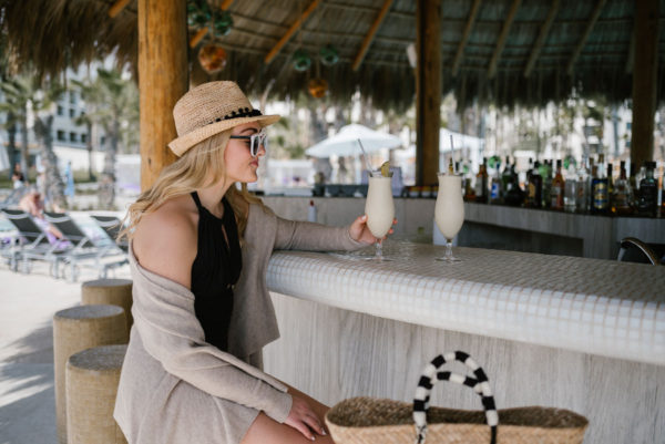 Travel blogger Bows & Sequins wearing a Vineyard Vines tassel cardigan, pom-pom fedora straw hat, black one-piece swimsuit, and Kayu Designs black and white straw tote.