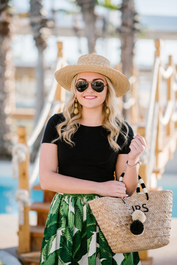 Travel blogger Bows & Sequins wearing a dressed down daytime outfit at a Cabo San Lucas hotel: black BP crop top tee, palm leaf skirt by Party Skirts, and a Kayu Designs straw tote.