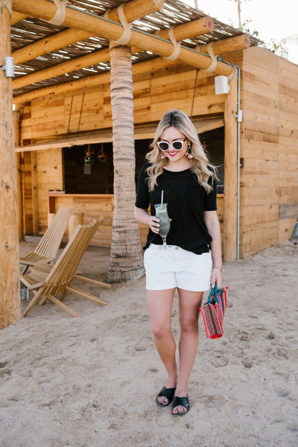 Travel blogger Bows & Sequins styling an Old Navy outfit with a black tee and white shorts on the beach in Cabo.