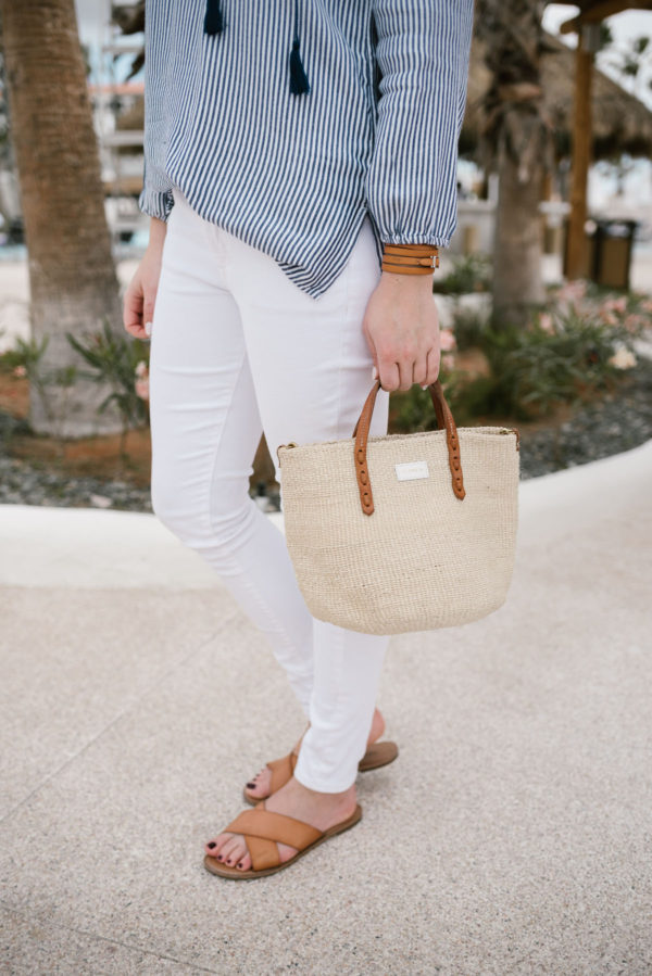 Bows & Sequins wearing white jeans from Old Navy with a Clare V Mini straw bag and slide sandals.