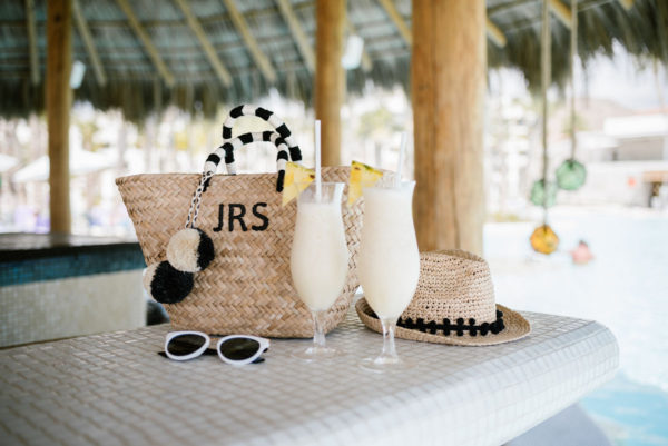 Kayu Designs monogrammed pom pom tote, pom-pom fedora, and black and white sunglasses at the swim-up bar at the Paradisus Los Cabos with pina coladas.