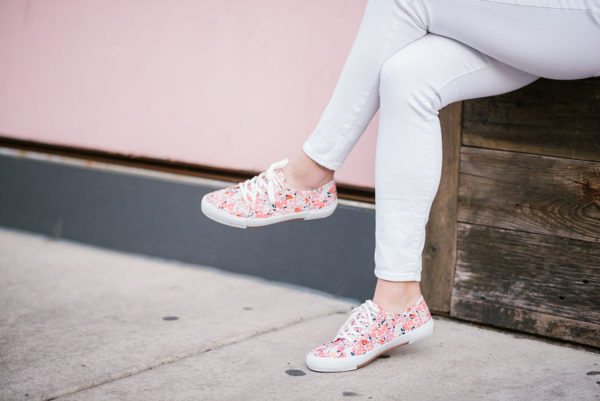 Bows & Sequins wearing white jeans and printed sneakers.
