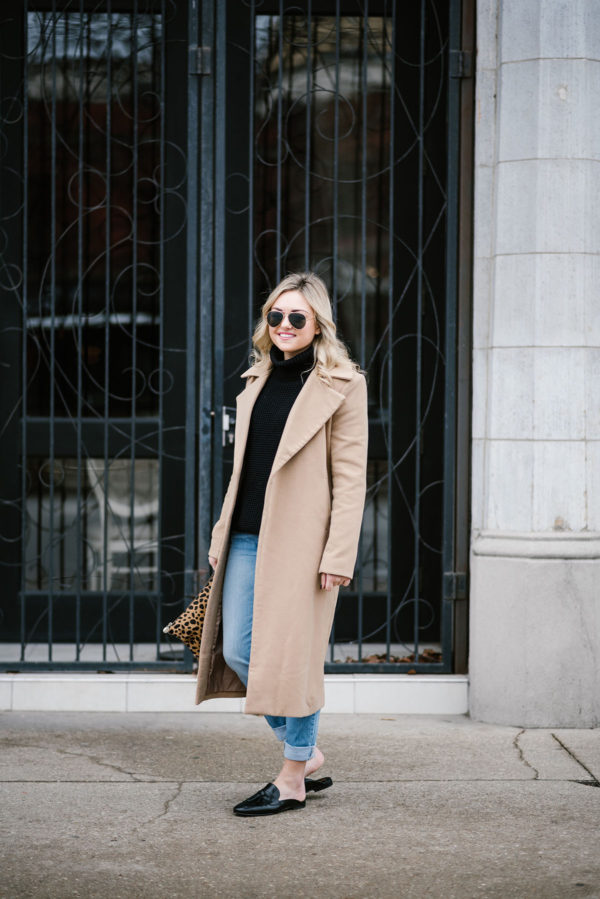 Bows & Sequins wearing a long camel coat with black leather slip-on loafers.