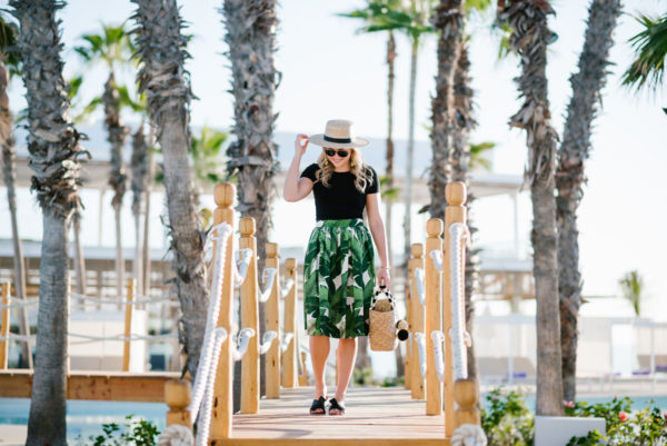 Blogger Bows & Sequins styling a Party Skirts palm leaf midi skirt with a Janessa Leone boater hat and Kate Spade bow sandals.