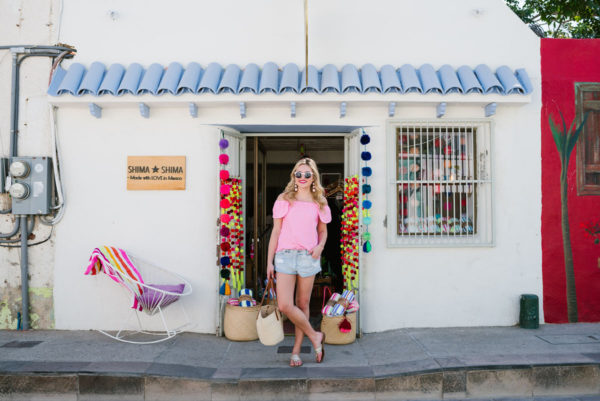 Bows & Sequins wearing a pink Vineyard Vines shirt and cut off jean shorts with Jack Rogers sandals in downtown San Jose del Cabo in front of Shima Shima store.