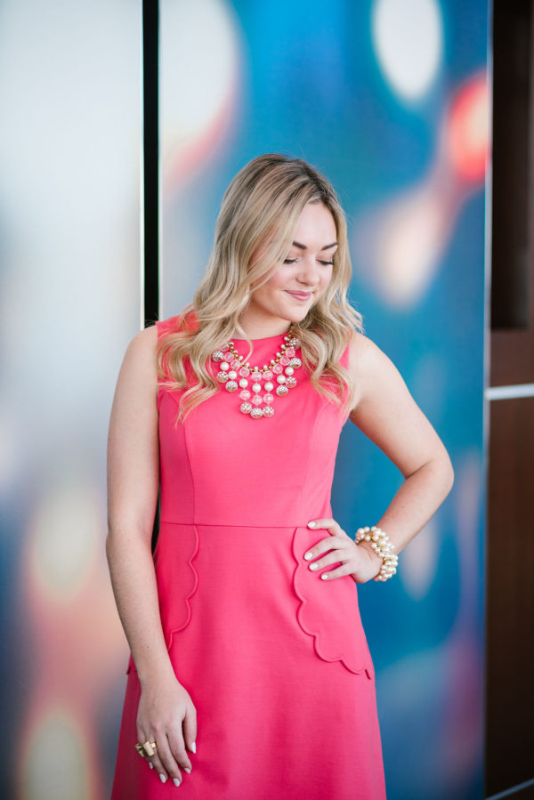 Bows & Sequins wearing a pink dress with a Kate Spade statement necklace.