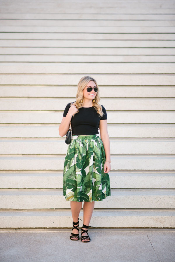 Bows & Sequins wearing a black Nordstrom BP tee shirt with a palm leaf skirt and Ray-Ban aviators.