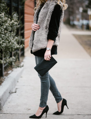 Fashion blogger Bows & Sequins wearing a faux fur vest over a black velvet blazer with grey skinny jeans and black pumps.