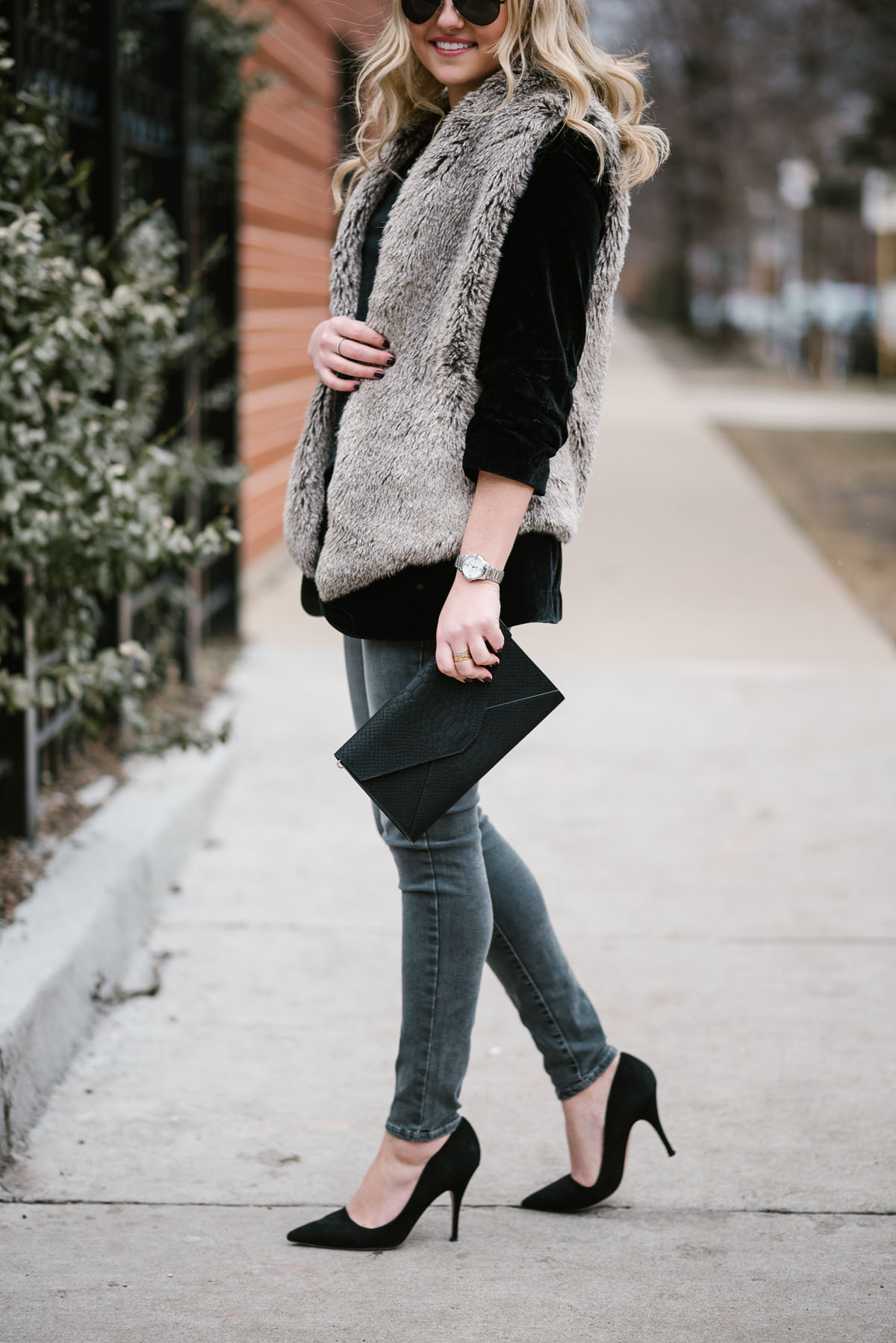 Fashion blogger Bows & Sequins wearing a faux fur vest over a black velvet blazer with grey skinny jeans and black pumps.