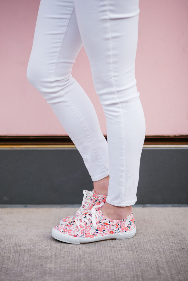 Bows & Sequins wearing white skinny jeans and printed floral sneakers.