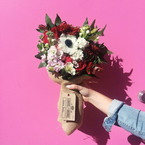 Bows & Sequins with a Flowers for Dreams bouquet in front of a pink wall.