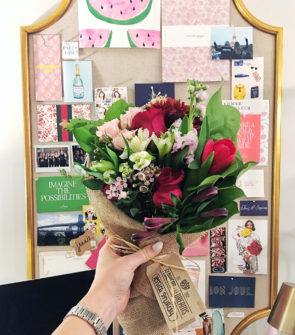 Bows & Sequins with a Flowers for Dreams bouquet in front of an inspiration bulletin board in creative office.