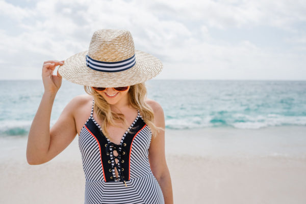 Bows & Sequins wearing a navy and orange one-piece swimsuit by the ocean in Cabo, Mexico.