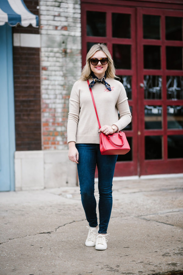 Travel blogger Bows & Sequins styling a french outfit with a neck scarf, Maje sweater, Celine sunglasses, and Sezane sneakers.