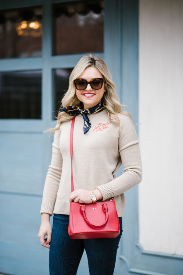Fashion blogger Bows & Sequins wearing a french Maje sweate with a silk neck scarf and a red crossbody bag.