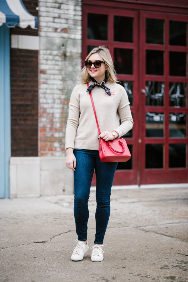 Chicago blogger Bows & Sequins wearing a Maje cashmere sweater, Sezane Jack sneakers, Celine sunglasses, a chic neck scarf, and a red Ralph Lauren crossbody bag.