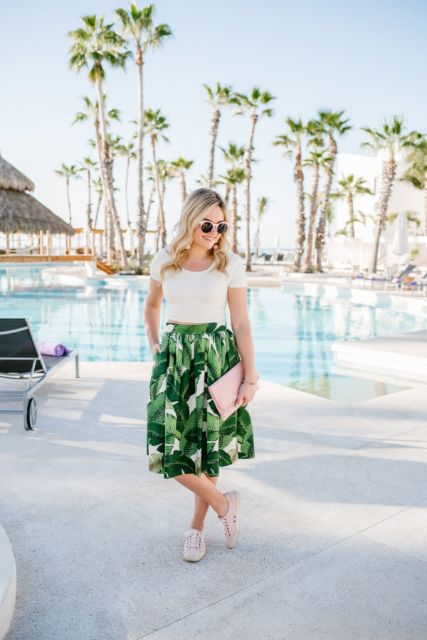 Bows & Sequins wearing a palm leaf patterned skirt with a pink crop top and pink sneakers in Cabo.