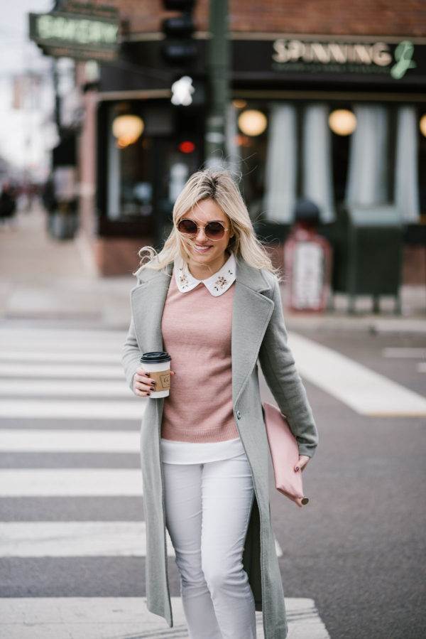 Fashion blogger styling blush pink sweater and white jeans.