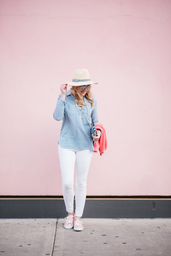 Bows & Sequins wearing a straw hat, striped shirt, and white jeans in front of a pink wall.