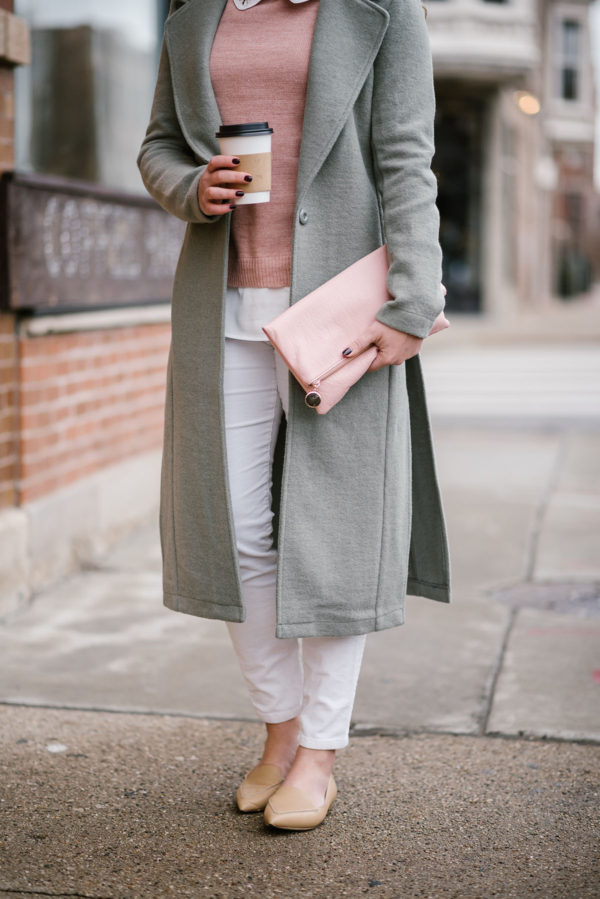 Fashion blogger Bows & Sequins wearing nude flats, white jeans, and long green coat.