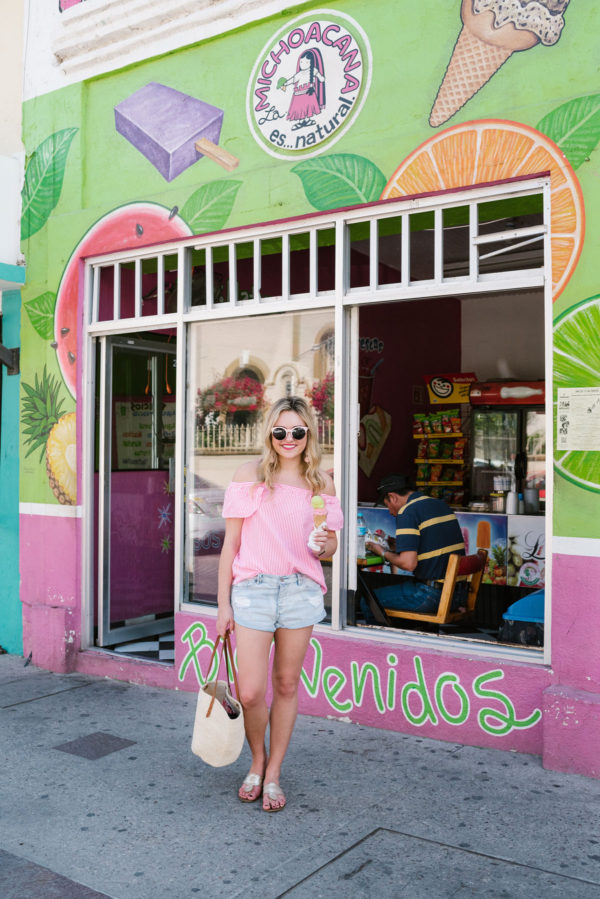 Bows & Sequins wearing a pink off the shoulder top from Vineyard Vines in front of colorful wall art in downtown San Jose del Cabo Mexico.
