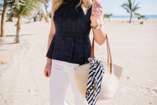 Travel blogger wearing a Sail to Sable blouse and white denim on a beach in Mexico with a straw tote and a silk scarf.