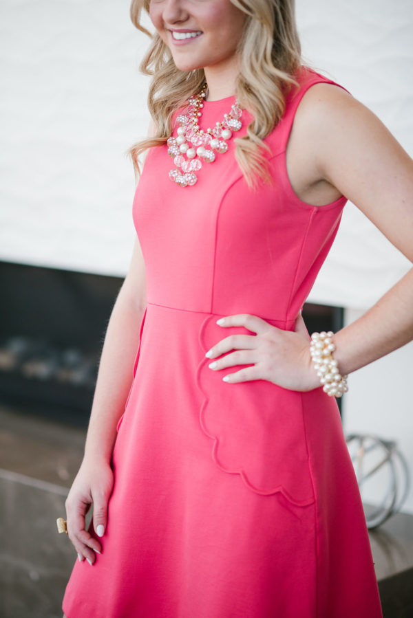 Bows & Sequins wearing a fit and flare dress with a statement necklace.