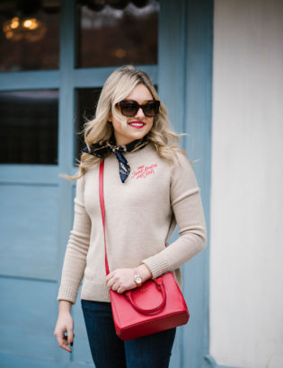 Fashion blogger Bows & Sequins styling a Parisian-inspired outfit... Maje sweater, Celine sunglasses, a silk neck scarf, and a red crossbody bag.