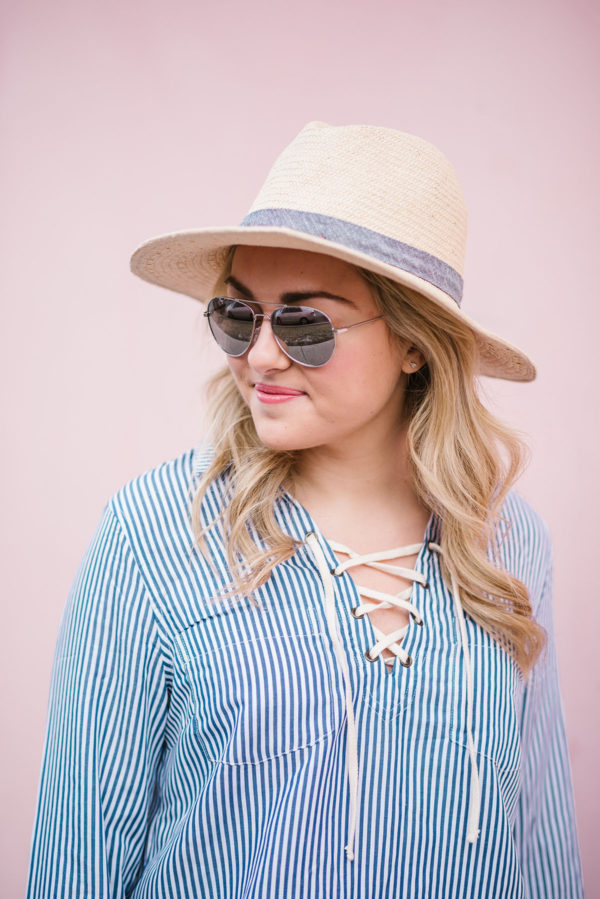 Bows & Sequins wearing a straw hat and mirrored aviator sunglasses.