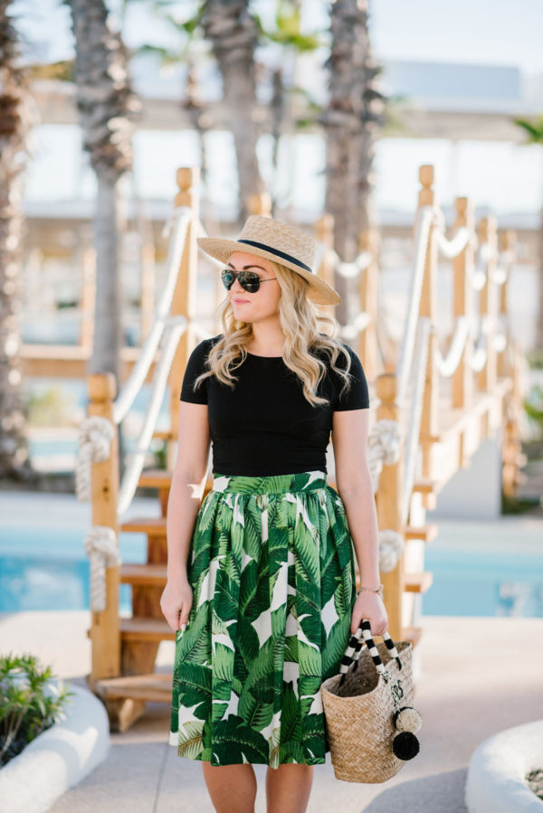 Chicago lifestyle blogger Bows & Sequins styling a Kayu straw tote with a Party Skirts classic palm leaf design with a black crop top.