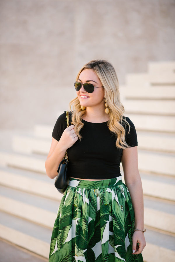 Bows & Sequins wearing a black crop tee with Tuckernuck gold statement earrings and a Gucci shoulder bag.