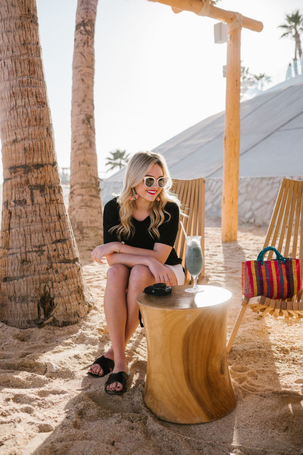 Travel writer Bows & Sequins wearing black criss cross sandals on the beach at Paradisus Los Cabos in Mexico.