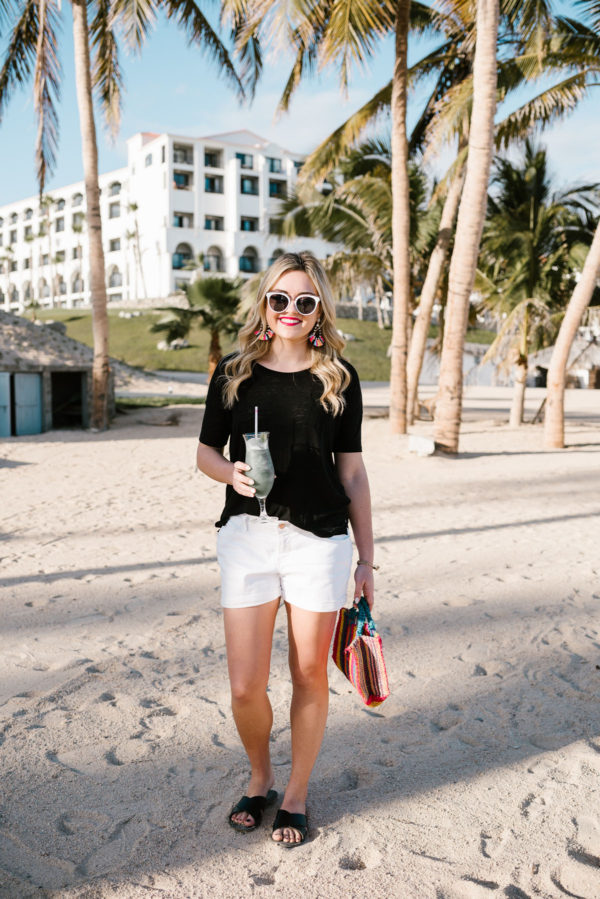 Lifestyle blogger Bows & Sequins wearing a casual black and white outfit with colorful Mexican tote on the beach with palm trees in Mexico.