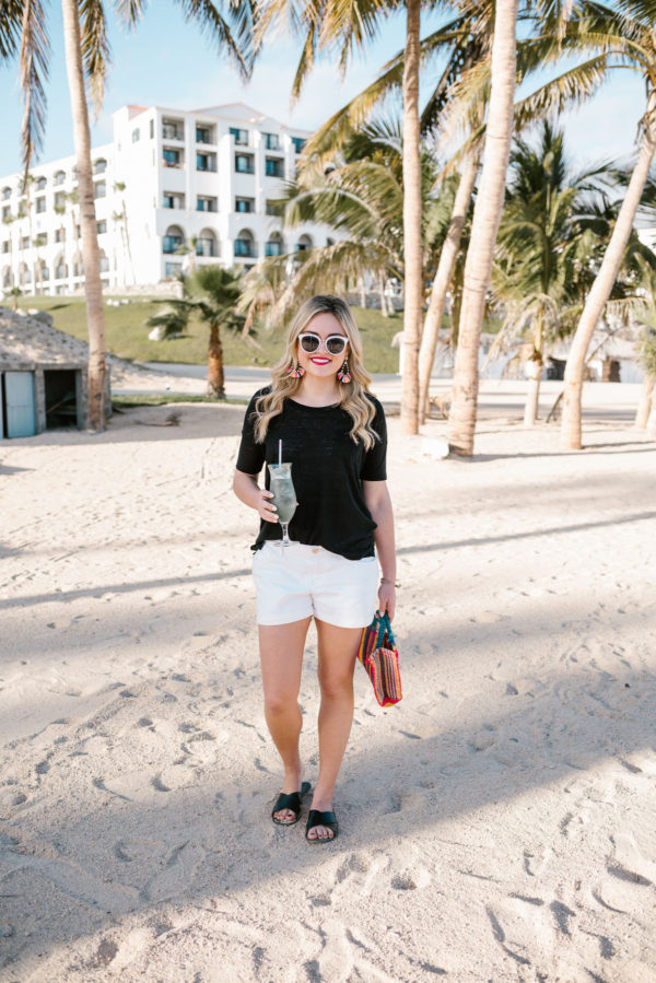 Bows & Sequins wearing a black boyfriend tee and white Old Navy shorts on the beach in Cabo with palm trees.