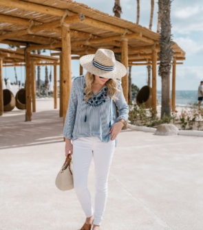 Bows & Sequins wearing an embroidered top from Old Navy, white jeans, and a Hat Attack sunhat.