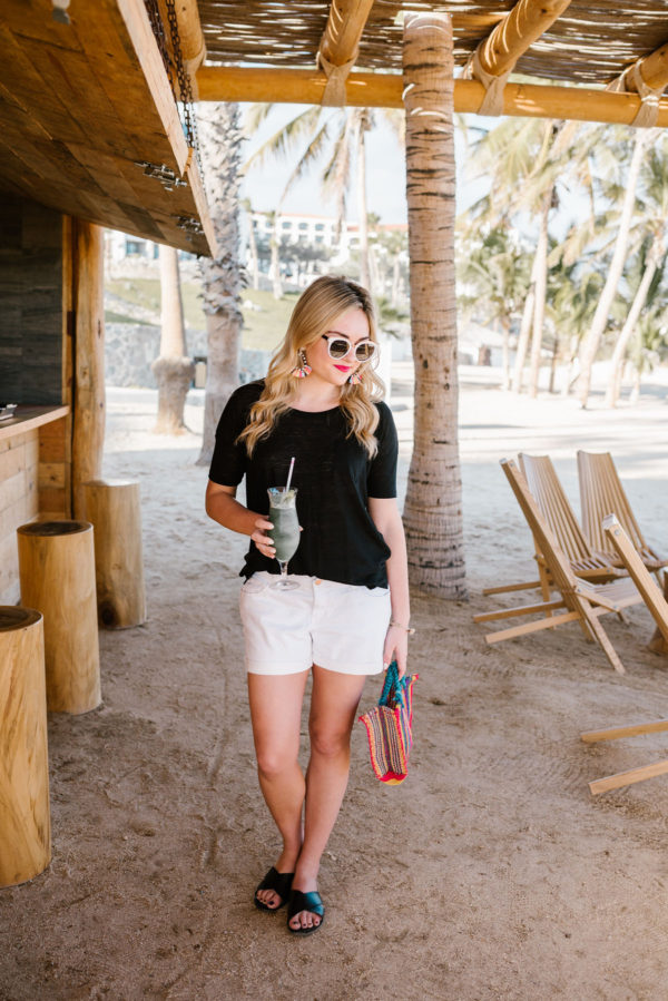 Bows & Sequins wearing black boyfriend tee and white boyfriend shorts on the beach in Cabo Mexico.