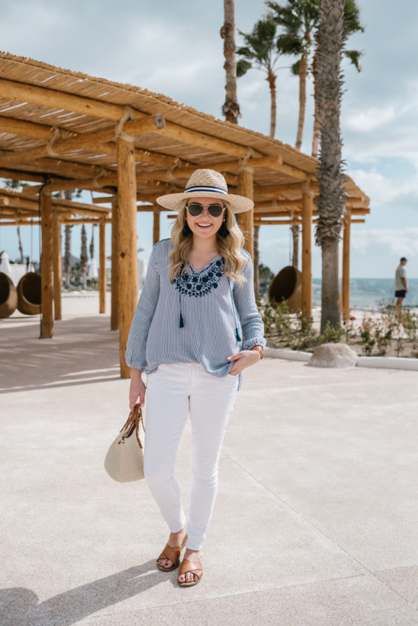 Bows & Sequins wearing a blue and white striped top with a Hat Attack summer hat and white jeans.