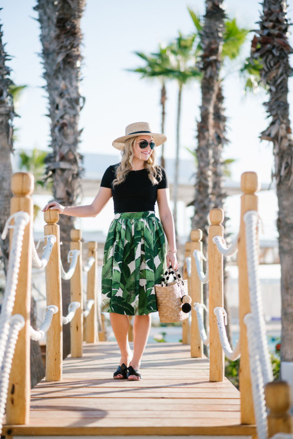 Blogger styling a black BP. crop tee with a boater hat and straw tote at the Paradisus hotel in Cabo San Lucas.